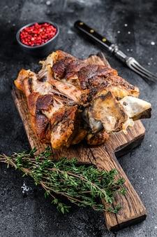 허브와 함께 나무 판자에 구운 돼지고기 너클 eisbein. 검은 배경. 평면도.