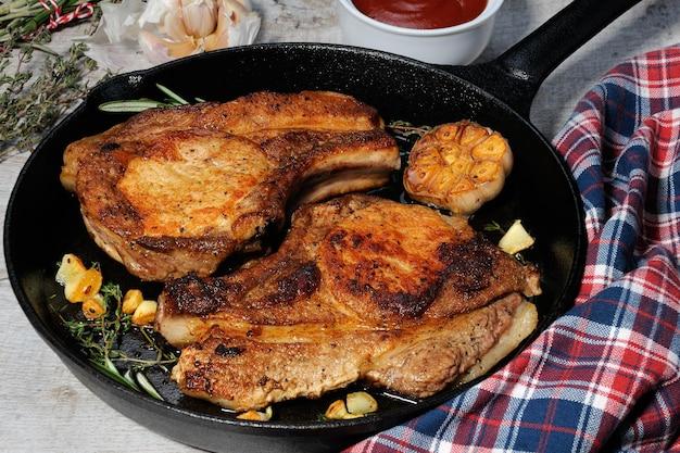 Жареный стейк из свиной корейки на сковороде с томатным соусом