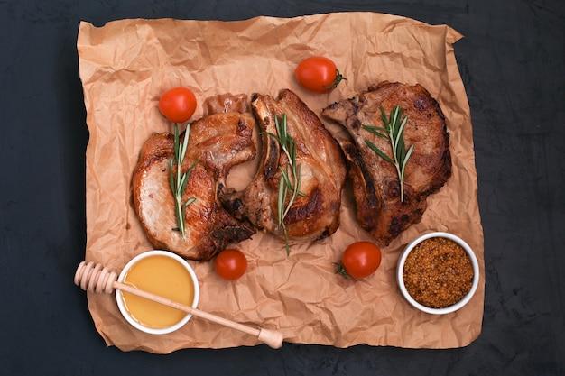 Жареные стейки из свиной корейки с зеленью и специями на бумаге для выпечки.