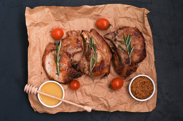 Roasted pork loin steaks with herbs and spices on baking paper.
