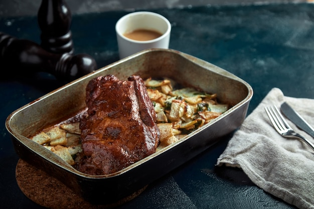 Roasted pork neck with baked potatoes and herbs on a tray on the black space