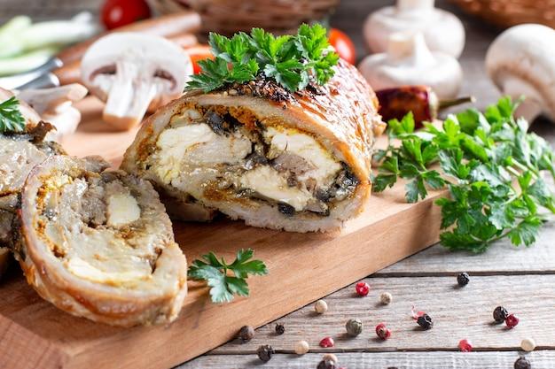 きのことチーズを詰めたローストポークロールに野菜を添えて木の板に盛り付けます