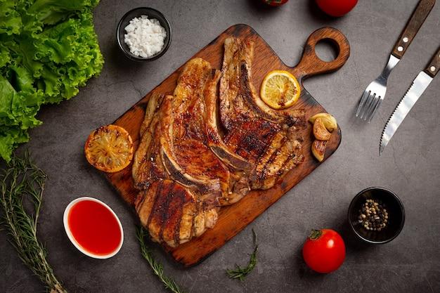 Bistecca di maiale arrosto sulla superficie scura.