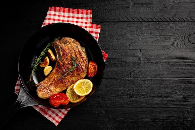 Bistecca di maiale arrosto sulla superficie di legno scuro.