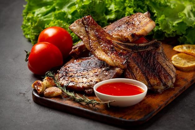 어두운 표면에 구운 돼지 고기 스테이크.