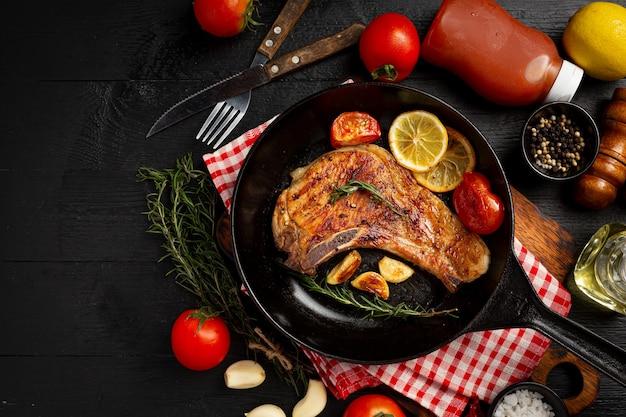 Жареный стейк из свинины на темной деревянной поверхности.