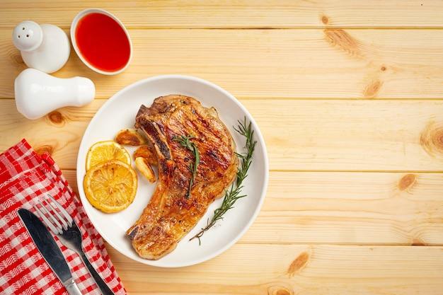Жареный стейк из свинины на деревянной поверхности.