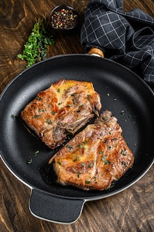 목살에서 프라이팬에 구운 돼지 고기 스테이크. 어두운 나무 배경입니다. 평면도.