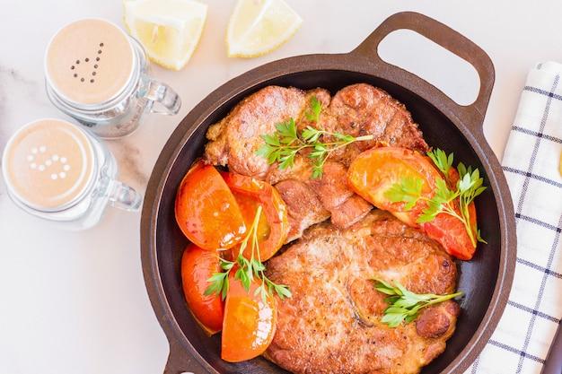 Жареные свиные стейки на сковороде из мяса шеи. светлый деревянный фон.