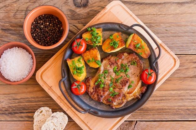 Жареные свиные стейки на сковороде из мяса шеи с картофелем. деревянный фон.