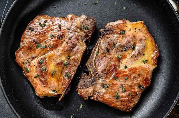 Жареные свиные стейки на сковороде из мяса шеи