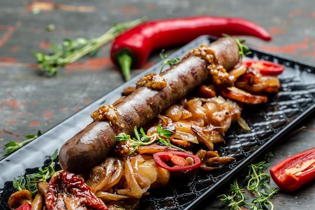 Жареный картофель и колбаса. обед, нарезанный ломтиками и обжаренный в масле, подается с перцем чили и горчицей на деревянном фоне. предпосылка рецепта еды. закройте вверх.