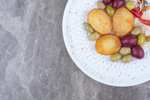白い皿にローストポテトと様々なピクルス。