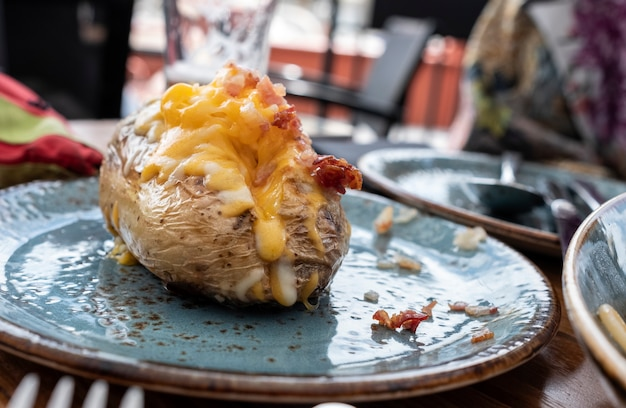 Roasted potato on blue plate stuffed with cheddar cheese and bacon