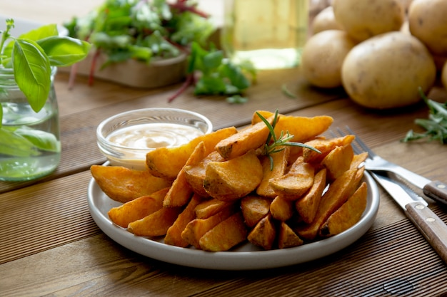 Roasted potato chips with sauce and herbs.