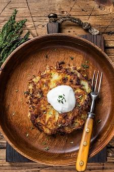 구운 감자 팬케이크 또는 나무 접시에 허브를 넣은 튀김