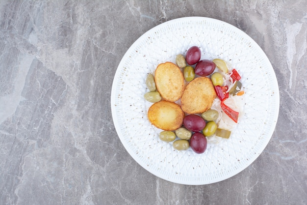 Roasted potato and various pickles on white plate.