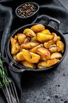 Жареные дольки картофеля с зеленью и розмарином. черный фон. вид сверху.