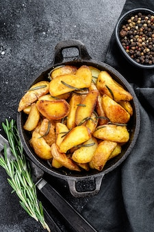 Roasted potato wedges with herbs and rosemary. black background. top view