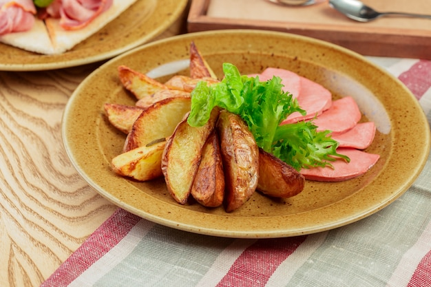 Roasted potatoes with ham slices close up