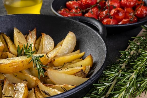 鉄のキャセロールにローズマリーを添えたローストポテトと、暗い背景にコンフィトマトのプレート。