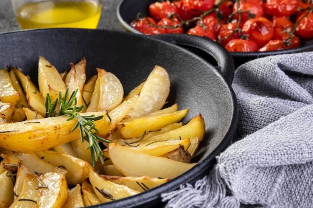 철 캐서롤에 로즈마리를 넣은 구운 감자와 어두운 배경에 콩피 토마토 한 접시.