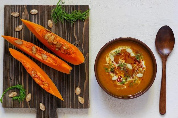 Zuppa di zucca e carote arrosto con crema, pepe nero e semi di zucca, tagliere e fette di zucca fresche, pane nero