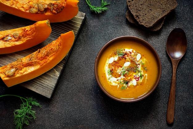 Zuppa di zucca e carote arrosto con panna, semi e verde fresco in ciotola di ceramica. vista dall'alto
