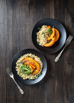 Roasted pumpkin salad with quinoa, kale, pine nuts in a black plate on wooden surface, top view