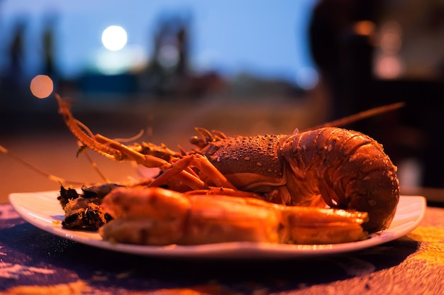배경이 흐릿한 새우가 있는 접시에 구운 붉은 랍스터. 레스토랑의 이국적인 해산물