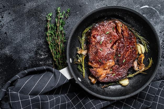 Жареный стейк рибай, говядина рибай в сковороде на черном столе. вид сверху.
