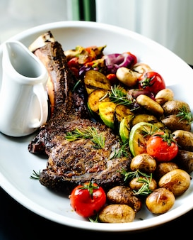 Жареное ребро с нарезанными жареными овощами и соусом