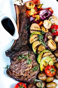 ローストリブとスライスしたフライド野菜とソース