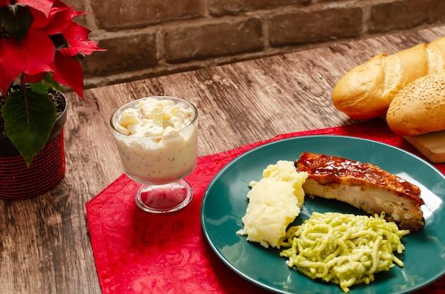 Жареные ребрышки, маринованные в соусе барбекю, подаются с картофельным пюре, спагетти и хлебом
