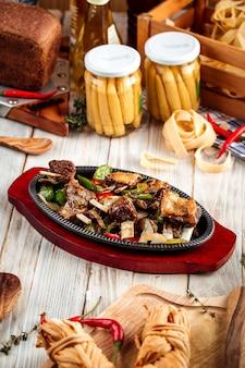 Жареные ребрышки с овощами в чугунной сковороде на деревянном столе