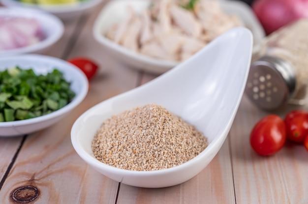 흰 숟가락에 볶은 쌀, 토마토 나무 테이블에 배치.