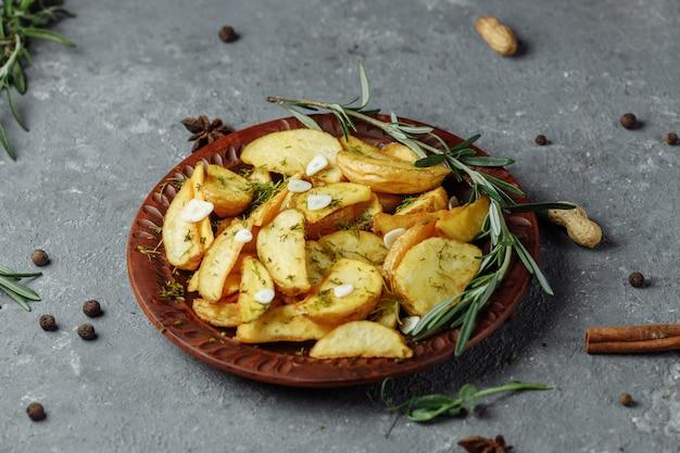 접시에 구운 된 로즈마리 마늘 감자 웨지.