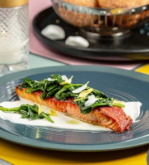 Roasted salmon on cream garnished with sauted spinach