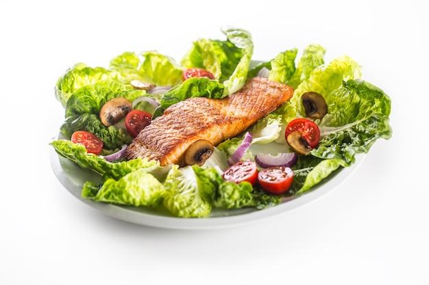 흰색 배경에 분리된 신선한 야채 샐러드를 곁들인 구운 연어 등심.