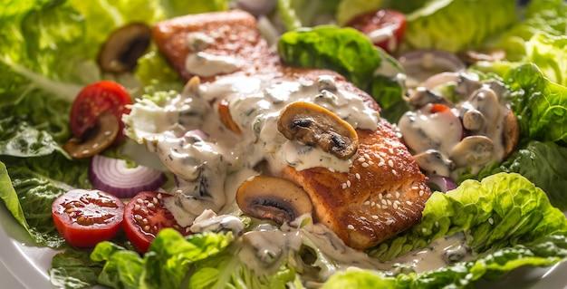 신선한 야채 샐러드 토마토 버섯 소스와 참깨를 곁들인 구운 연어 필레.