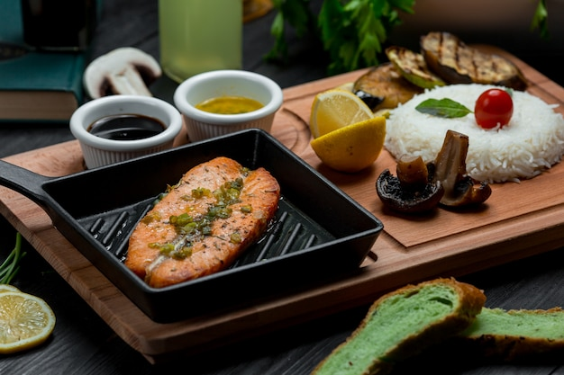 Roasted salmon in an ironic pan served with teriyaki sauce
