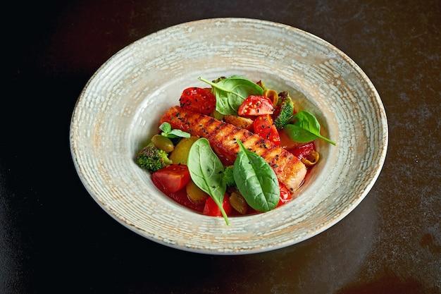 Стейк из лосося в томатном соусе с тушеными овощами на гарнир. выборочный фокус, черный фон