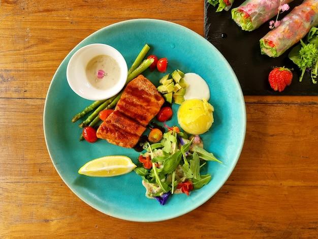 폴렌타 슬라이스 레몬과 꽃 샐러드 롤과 같은 혼합 샐러드와 구운 연어 스테이크