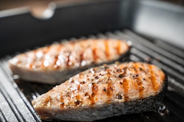Жареные стейки из лосося на сковороде, вид сверху.