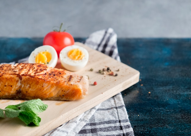 Roasted salmon with boiled egg on blue table