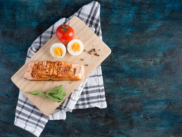 Roasted salmon with boiled egg on board