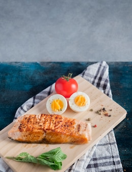 Roasted salmon with boiled egg on wooden board