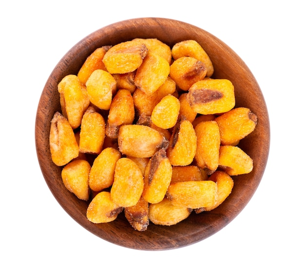 Roasted salted corn nuts in wooden bowl, isolated on white background. beer snack, dry corn with spices. top view.