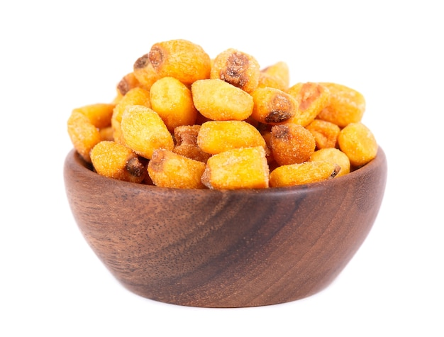 Roasted salted corn nuts in wooden bowl, isolated on white background. beer snack, dry corn with spices.