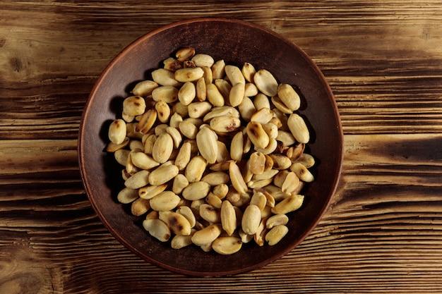 Жареный соленый арахис в тарелке на деревянном столе. вид сверху